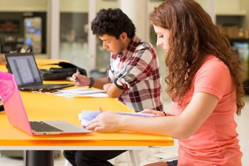 Two college students studying at a table with laptops