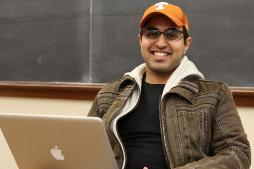 Student with UT cap working on his laptop