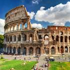 Photo of the Roman Colosseum ruins with tourists walking around the site.