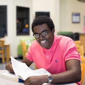 Student with pink polo shirt and glasses sitting in front of a book smiling at the camera