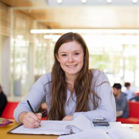 Girl sitting with a binder in front of her and pen in her right hand as she smiles for the camera